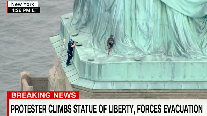 Illustration for article titled A Black Woman in Handcuffs For Climbing The Statue of Liberty on Independence Day is a Perfect Metaphor For America