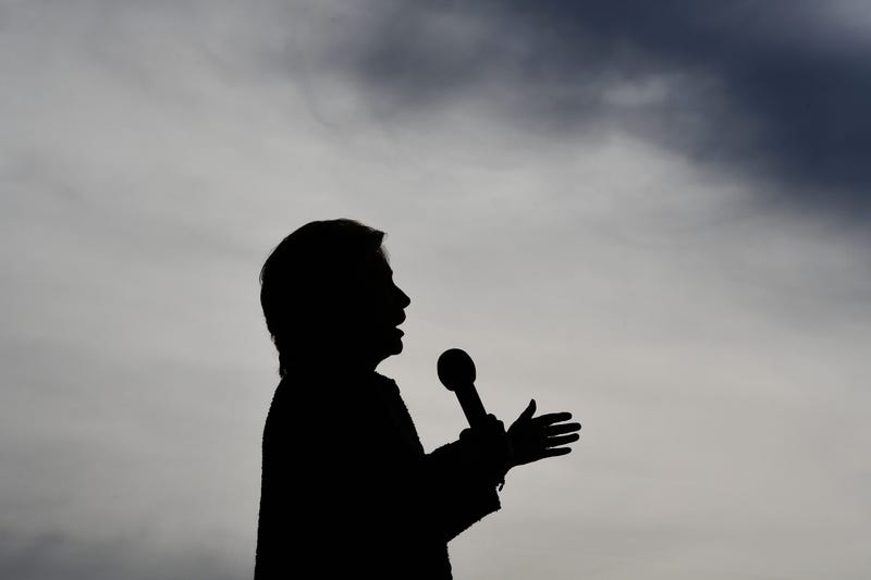 """Democratic presidential nominee Hillary Clinton seen in silhouette as she speaks at a Democratic party """"Women Win"""" early-vote rally in Cedar Rapids, Iowa, on Oct. 28, 2016.  The FBI dealt Hillary Clinton's seemingly unstoppable White House campaign a stunning blow Oct. 28 by reopening a probe into her use of a private email server while she was secretary of state. JEWEL SAMAD/AFP/Getty Images"""
