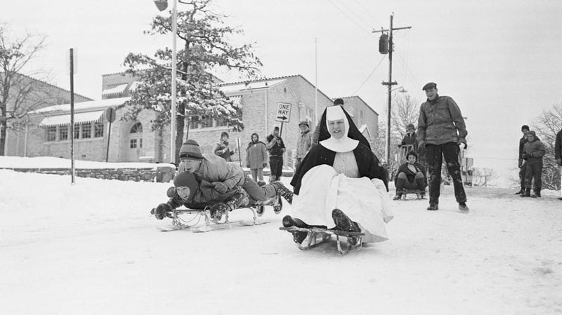 Sister Monica rides a sled with children