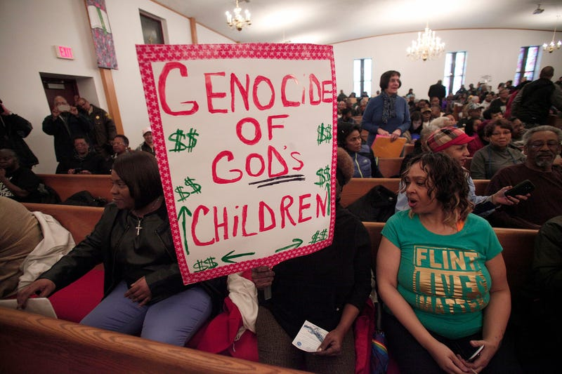 A woman holds a sign at a prayer service in Flint, Mich., before participating in a national mile-long march to highlight the push for clean water in Flint on Feb. 19, 2016. (Bill Pugliano/Getty Images)