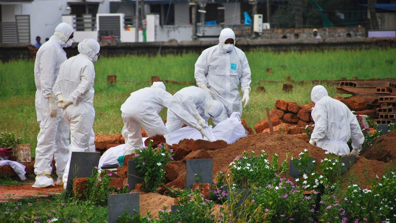 Paramedics prepare to bury a victim of the Nipah virus outbreak in Kerala, India.
