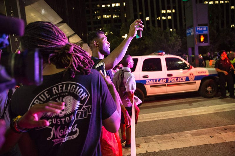 Bystanders stand near police barricades following the sniper shooting in Dallas on July 7, 2016.  LAURA BUCKMAN/AFP/Getty Images