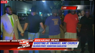Individuals praying at the scene where a white gunman opened fire inside a historic black church in Charleston, S.C., June 17, 2015, killing nine people.WCSC