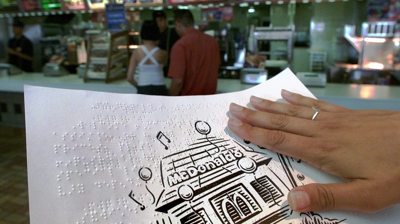 A patron at a Toronto McDonald's holds the restaurant's braille menu.
