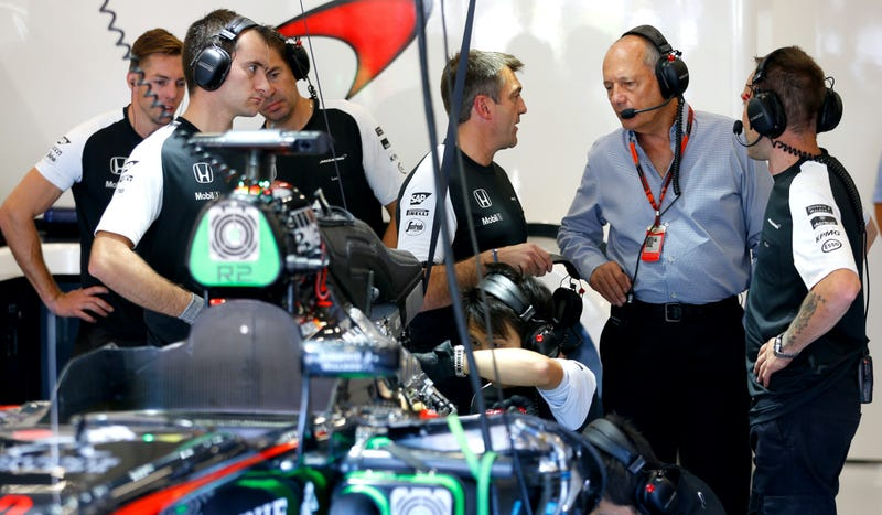 Ron Dennis (in grey) speaking with members of the McLaren Formula One team. Photo credit: Charles Coates/Getty Images