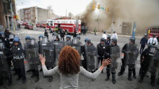 A woman faces down a line of Baltimore police officers in riot gear during violent protests following the funeral of Freddie Gray, April 27, 2015, in Baltimore. Chip Somodevilla/Getty Images