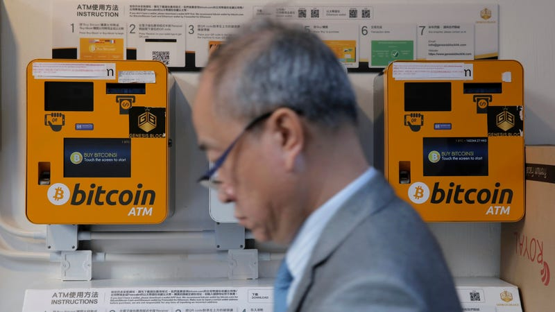 A man passes a bitcoin ATM in Hong Kong on December 21st, 2017. Photo: AP