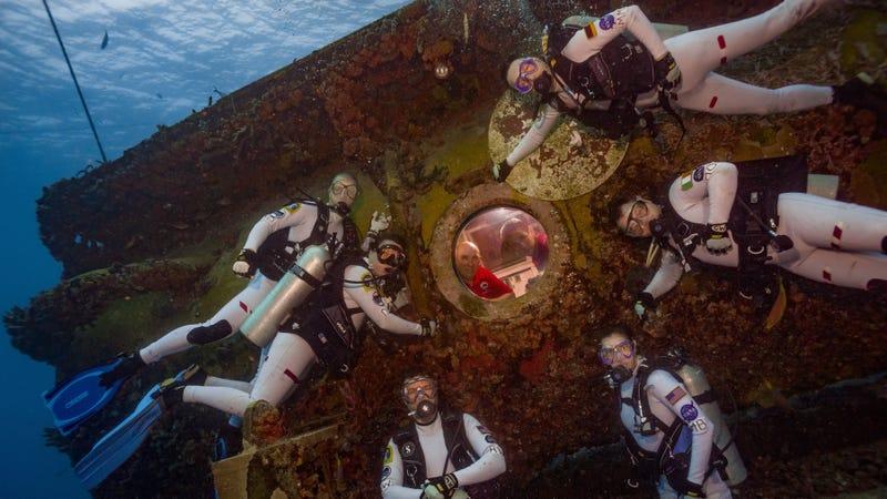 A group of astronauts in training surrounding the undersea Aquarius laboratory. Image: NASA