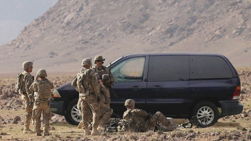 Troops standing next to their Ford Windstar.