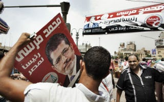 Supporters hold sign of Mohamed Morsi. (Marco Longari/AFP/Getty Images)