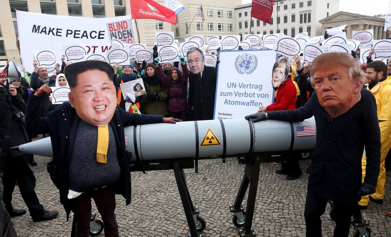 An activist with a mask of Kim Jong Un, chairman of the Workers' Party of Korea and supreme leader of North Korea, and another with a mask of President Donald Trump march with a model of a nuclear rocket during a demonstration against nuclear weapons on Nov. 18, 2017, in Berlin.