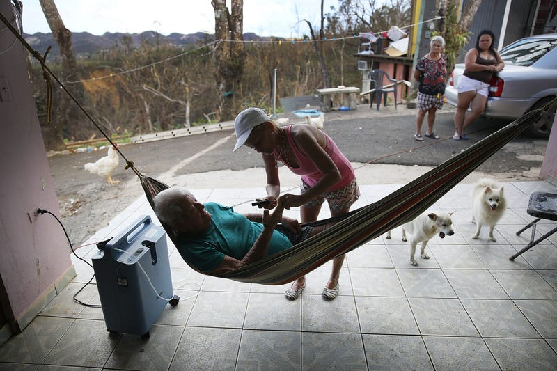 Irma Maldanado checks on her father, Ignacio Maldanado Ortiz, who uses an oxygen machine because of his emphysema on Oct. 2, 2017, in Corozal, Puerto Rico. Irma Maldanado said her father is in need of oxygen but has no way of getting a supply in the aftermath of Hurricane Maria. (Joe Raedle/Getty Images)