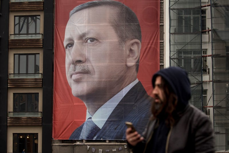 People walk past a large banner showing the portrait of Turkish President Recep Tayyip Erdogan in Taksim Square on March 13, 2017 in Istanbul, Turkey  (Photo by Chris McGrath/Getty Images)