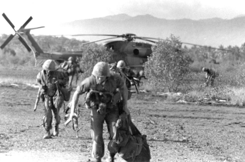 Unidentified U.S. Marines run from a HH-53C helicopter during the SS Mayaguez operation. Photo credit Wikimedia Commons