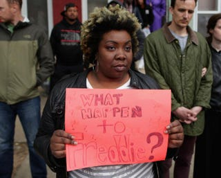 A demonstrator from Baltimore's Sandtown neighborhood holds a sign seeking answers in the death of Freddie Gray, across the street from the Baltimore Police Western District station, during a protest against police brutality and Gray's death.Chip Somodevilla/Getty Images