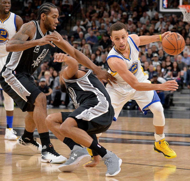Stephen Curry drives around Kawhi Leonard and a staggering Patty Mills. Via AP.