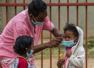 Face masks are placed on children in Antananarivo, Madagascar, on Oct. 3, 2017. (Alexander Joe/AP Images)