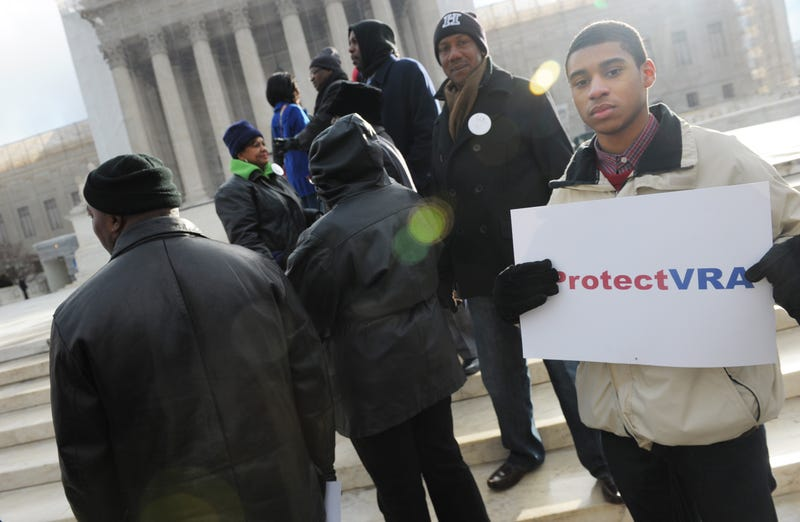An activist holds a pro-voting-rights placard outside the Supreme Court on Feb. 27, 2013, in Washington, D.C., as the court prepares to hear Shelby v. Holder. MANDEL NGAN/AFP/Getty Images