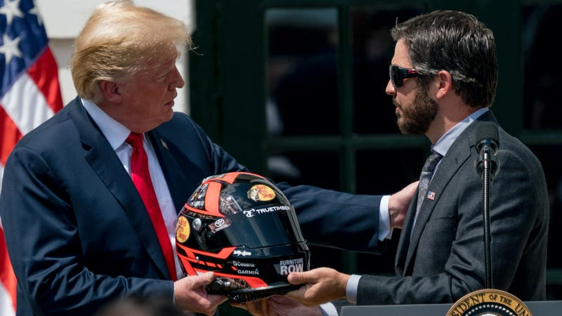 2017 NASCAR Cup winner Martin Truex Jr. presents Donald Trump with a helmet at an event honoring Truex's win at the White House.