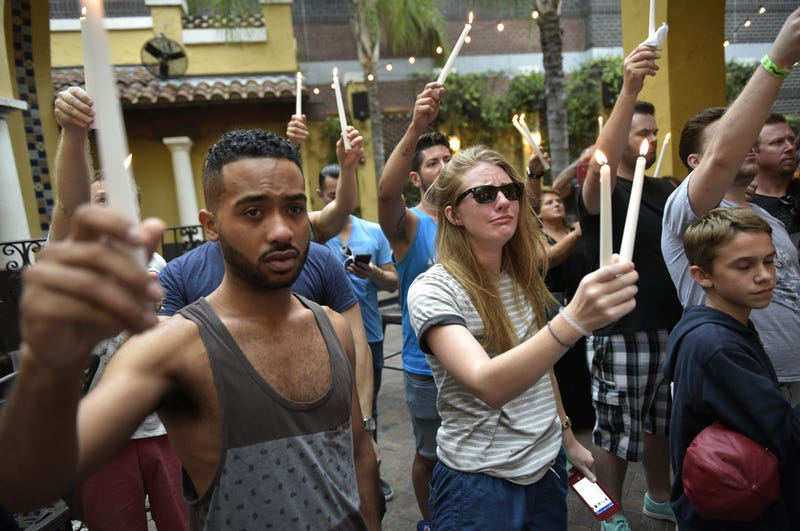 People hold candles during a vigil at the Ember restaurant and bar in Orlando, Fla., on June 12, 2016, for the victims of the Pulse club shooting in Orlando.MANDEL NGAN/AFP/Getty Images