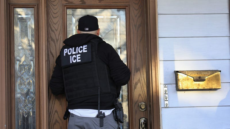 An ICE officer conducting a search.
