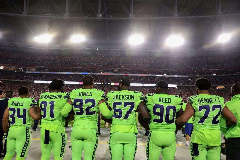 Members of the Seattle Seahawks, including defensive end Michael Bennett, No. 72, link arms during the national anthem for the NFL game against the Arizona Cardinals at University of Phoenix Stadium  in Glendale, Ariz., on Nov. 9, 2017. (Christian Petersen/Getty Images)