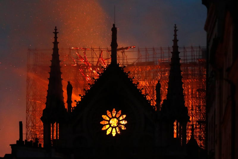 The glow of flames can be seen through the windows of Notre Dame as fire ravaged the centuries-old cathedral in Paris April 15, 2019.
