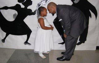 A child and her father attend the first daddy-daughter dance at the Federal Detention Center Miami Nov. 4, 2014.Federal Detention Center Miami
