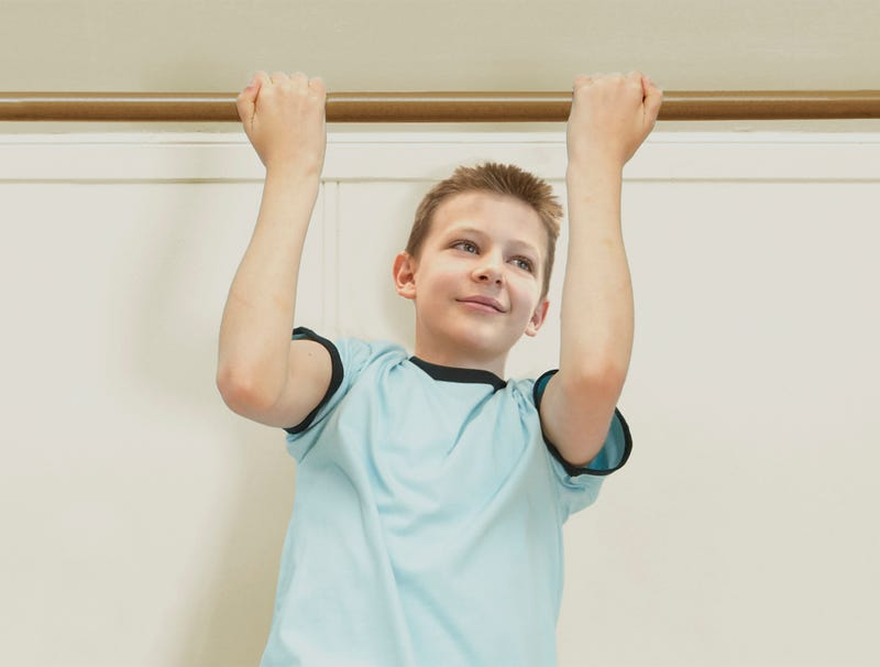A second-grade boy does pull-ups.