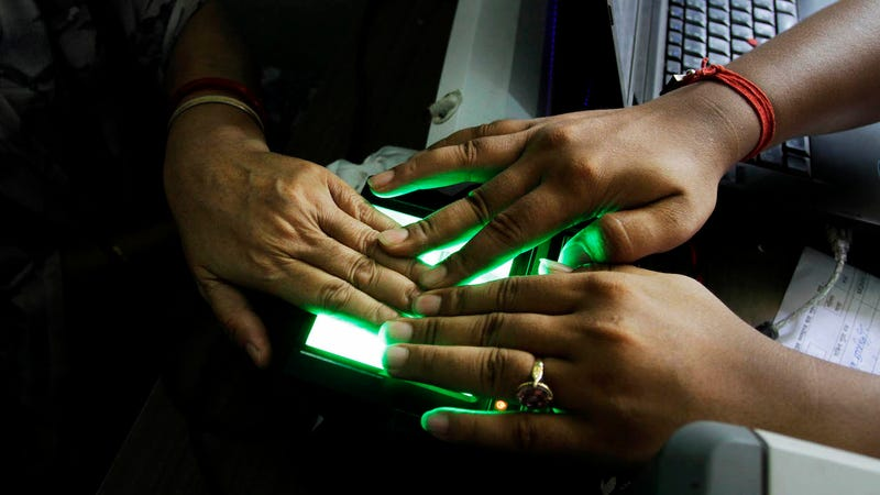 An operator helps an elderly woman scan her fingerprints as she enrolls for Aadhar. (Photo: AP)