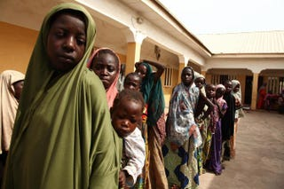 Girls rescued by Nigerian soldiers from Islamist militants Boko Haram at Sambisa Forest line up to collect donated clothes at the Malkohi refugee camp in Yola, Nigeria, on May 5, 2015.EMMANUEL AREWA/AFP/Getty Images