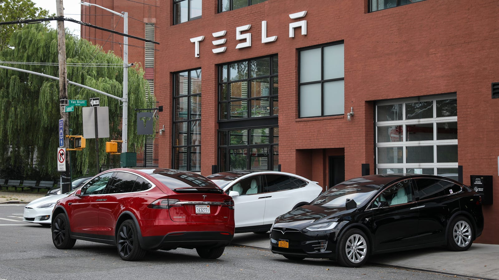 Tesla Model X at the front of a Tesla Store