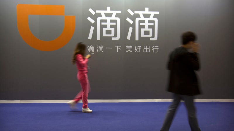 People walk past a Didi Chuxing sign at the Global Mobile Internet Conference in Beijing in 2017.