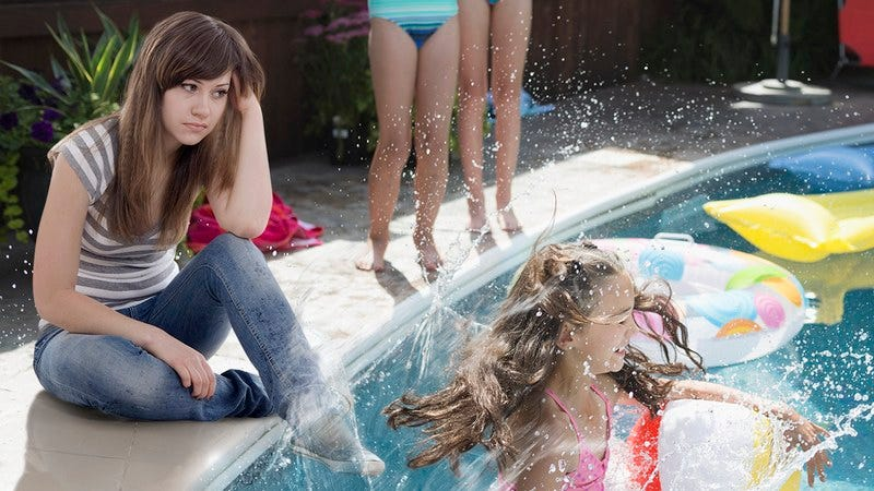 A young girl sitting next to a pool filled with kids.