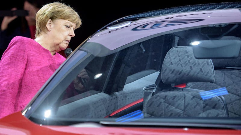 FRANKFURT AM MAIN, GERMANY - SEPTEMBER 14: The German Chancellor Angela Merkel looks into a Volkswagen ID Crozz electric crossover concept car during her visit at the 2017 Frankfurt Auto Show 'Internationale Automobil Ausstellung' (IAA) on September 14, 2017 in Frankfurt am Main, Germany. The Frankfurt Auto Show is taking place during a turbulent period for the auto industry. Leading companies have been rocked by the self-inflicted diesel emissions scandal. At the same time the industry is on the verge of a new era as automakers commit themselves more and more to a future that will one day be dominated by electric cars