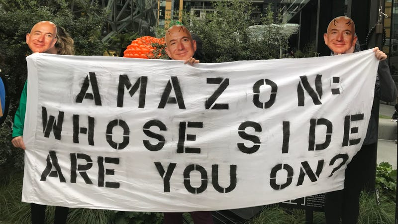 Illustration for article titled Dozens of Jeff Bezoses Protest Amazon's Continued Relationship With ICE
