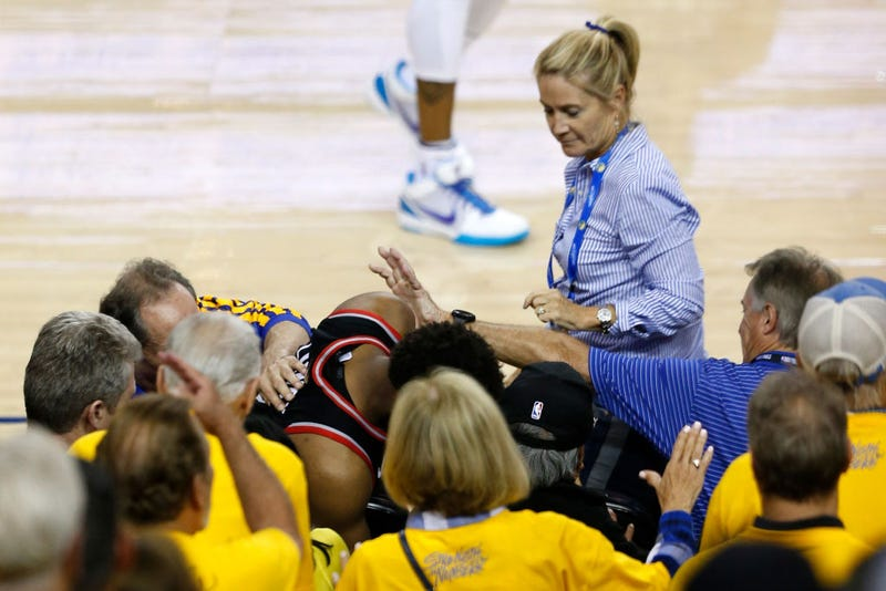Kyle Lowry of the Toronto Raptors is pushed by Warriors minority investor Mark Stevens (blue shirt) after falling into the seats after a play on June 05, 2019 in Oakland, Calif.