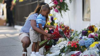 Tamara Holmes and her son Trenton Holmes lay flowers in front of Emanuel African Methodist Episcopal Church in Charleston, S.C., after a mass shooting at the church that killed nine people June 18, 2015.Joe Raedle/Getty Images