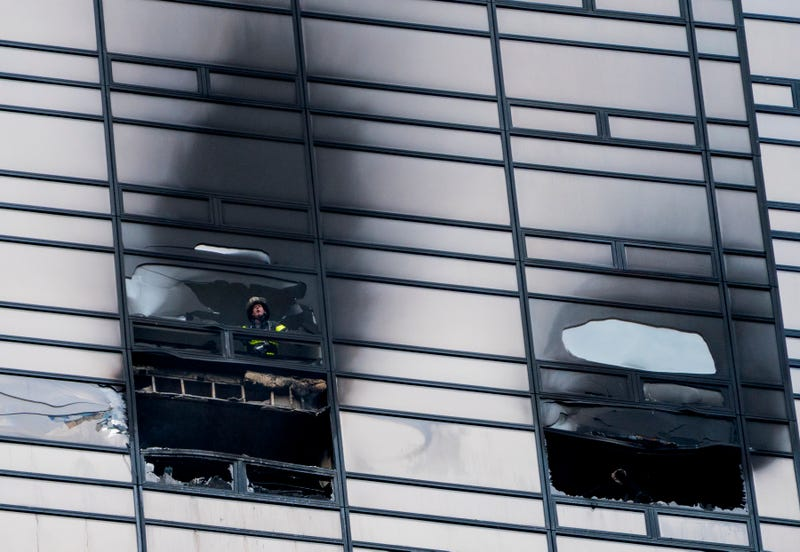 A firefighter looks out from the window of a damaged apartment in Trump Tower in New York City on April 7, 2018..