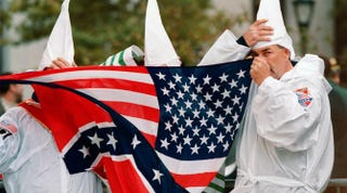 Three members of the Ku Klux Klan hide behind a combination Confederate and American flag Oct. 23, 1999, in New York.DOUG KANTER/AFP/Getty Images