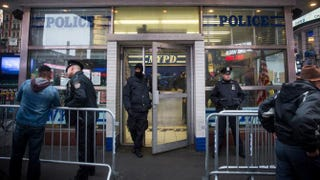 Police officers stand guard outside a New York City Police Department substation in Times Square Dec. 22, 2014. Andrew Burton/Getty Images