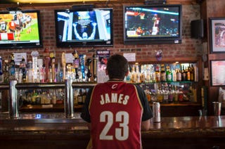 A fan watches news coverage of LeBron James' impending return to Cleveland in downtown Cleveland on July 11, 2014.Angelo Merendino/Getty Images