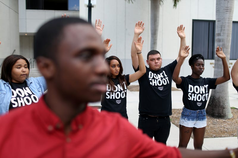 """Protesters raise their arms and shout """"Hands up, don't shoot' outside the James Lawrence King Federal Justice Building, where the U.S. Attorneys Office, Southern District of Florida, is located, on Aug. 14, 2014, in Miami. The protesters included members of the civil rights group Dream Defenders. (Joe Raedle/Getty Images)"""