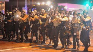 Law-enforcement officers watch during a protest on West Florissant Avenue in Ferguson, Mo., on Aug. 18, 2014, in the wake of the fatal police shooting of Michael Brown. Michael B. Thomas/AFP/Getty Images