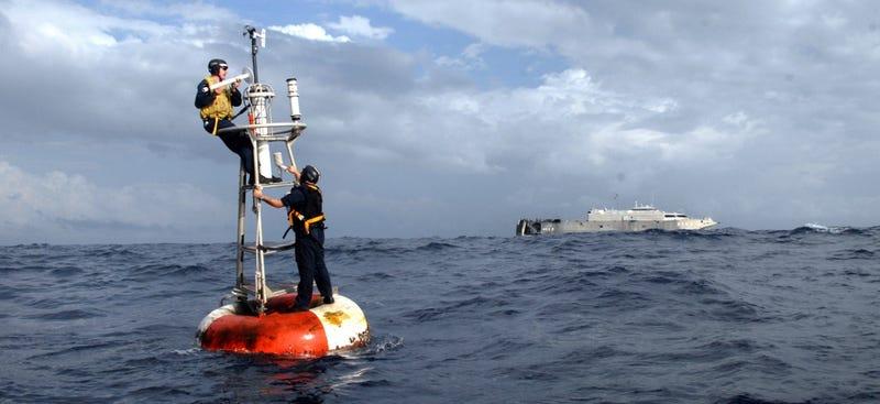 Dos técnicos reparan una boya Atlas como la que marca Null Island. Foto: NOAA