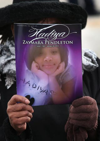 Minister Elnor Brown holds up the funeral program for 15-year-old Hadiya Pendleton outside Chicago's Greater Harvest M.B. Church during funeral services for the teen Feb. 9, 2013.Scott Olson/Getty Images