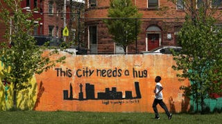 A child runs past a mural in West Baltimore on May 3, 2015, two days after Baltimore authorities released a report on the death of Freddie Gray.Patrick Smith/Getty Images