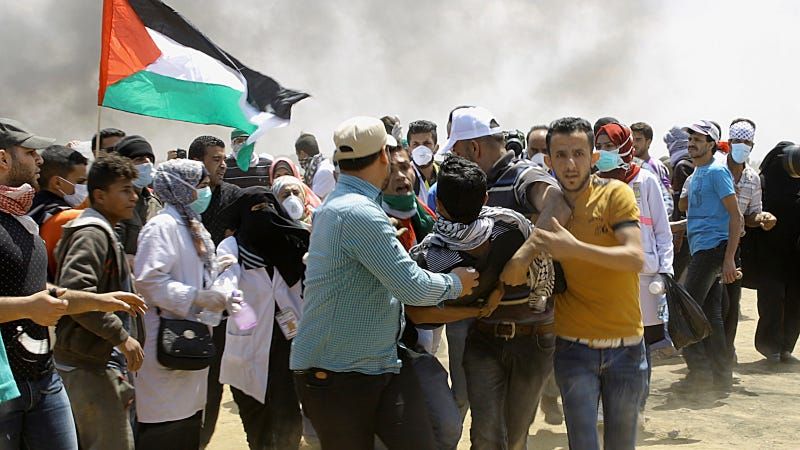 Palestinian protesters evacuate a wounded youth near the Israeli border fence, east of Khan Younis, in the Gaza Strip, Monday, May 14, 2018. Thousands of Palestinians are protesting near Gaza's border with Israel, as Israel prepared for the festive inauguration of a new U.S. Embassy in contested Jerusalem.