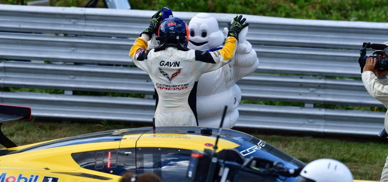 Driver Oliver Gavin high-fives Bibendum next to the race-winning No. 4 Corvette. Photo credit: IMSA