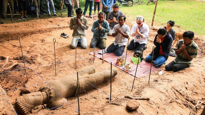 Archaeologists hold a religious ceremony to ask the spirit protecting the site for permission to move the statue. (Image: Apsara Authority via The Cambodia Daily)